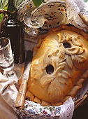 Duck pie with pastry leaf decoration on wicker tray
