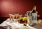 A few glasses of champagne, bottle in ice bucket, grapes