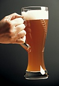 A Hand Holding a Tall Glass of Wheat Beer