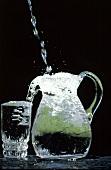 Wasser fliesst in eine Kanne & Trinkglas