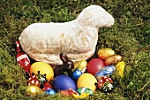Easter lamb, coloured eggs and sweets in Easter nest