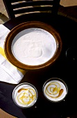 Yoghurt in dish and two bowls of yoghurt with honey