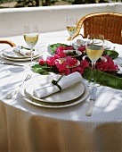 Laid table with tapas on banana leaves and flowers