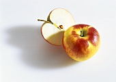 Whole and half a red and yellow apple
