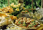 Spring buffet with various snacks, champagne & tulips