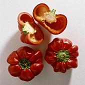 Drei rote Paprikaschoten (Tomatenpaprika), eine halbiert