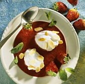 Poached meringues with flaked almonds, mint on strawberry sauce