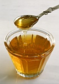 Honey Pouring From a Spoon into a Cup