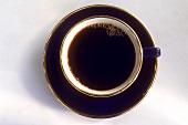 Schwarzer Kaffee in dunkelblauer Tasse mit Goldrand