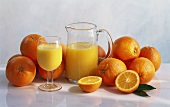 Orange Juice in a Glass and Pitcher; Surrounded by Fresh Oranges