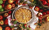 Turned-out apple tart with icing sugar and baskets of apples