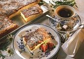 Cake with quark filling & icing sugar & a cup of coffee