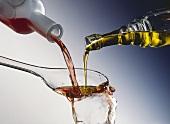 Essig & Öl aus Flaschen zusammen in einen Salatlöffel gießen