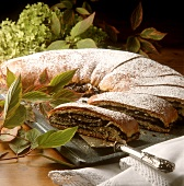 Poppy seed strudel with icing sugar on the baking sheet