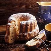Gugelhupf with raisins & icing sugar on wooden background