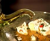 Schafskäse wird mit Olivenöl, Kräutern & Gewürzen mariniert
