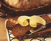 Rye bread slices with butter rolls and butter knife