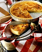 Quiche Lorraine in baking dish and one piece on plate