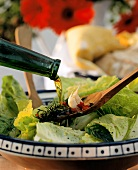 Pouring oil from bottle on to wooden spoon above salad plate