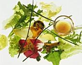 Single salad leaves, chanterelles, vinaigrette on ladle