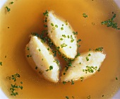 Semolina dumplings (detail) in clear broth with snipped chives