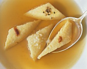 Vienna cheese dumplings as soup addition in broth with spoon