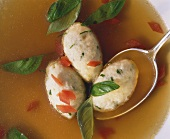 Quark and basil dumpling with spoon in clear broth