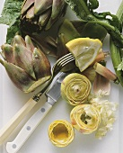 Artichokes, whole and hollowed out, with knife, fork & lemon