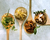 Several different risotto dishes on wooden spoons