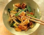 Fried tofu on vegetables (carrots, broccoli, mangetouts)