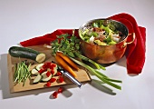 Vegetables on chopping board & in pan with strainer insert