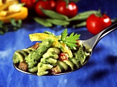 Spoonful of pasta salad with olive paste, pepper, green beans