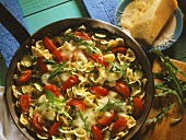 Courgette farfalle with cherry tomatoes & rocket in pan