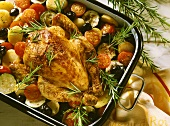 Rosemary chicken on a bed tomatoes, olives, potatoes