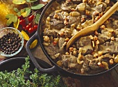 Wild boar ragout in the pot with a wooden spoon