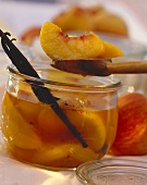 Oranges and peaches with vanilla sticks in open jar