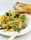 Penne with herb & cheese sauce on plate, décor: baguette