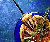 Pizza with sardines and sprig of rosemary on blue plate