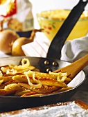 Potato noodles in pan & on spatula with onions