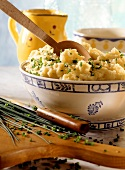 Mashed potato with chives in dish with wooden spoon
