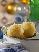 Thuringian dumplings on ladle at edge of pan