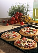 Small sauerkraut pizzas with tomatoes & olives on baking sheet