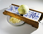 Halved white cabbage on cabbage slicer & shredded cabbage