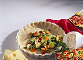 Unbaked vegetable quiche in baking dish, with ingredients