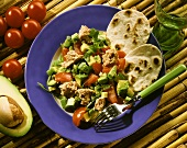 Tacos with tuna salad, avocados & tomatoes on plate