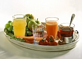 Various juices & tea in glass with fruit, vegetables on tray
