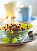 Millet muesli with date mousse & lemon balm in glass bowl