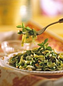 Green ribbon noodle salad with spring onions & pine nuts