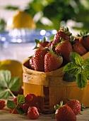 Fresh strawberries in chip basket, raspberries beside it