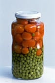 Carrots and peas in jar on light background